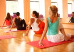 Women practicing yoga at health club